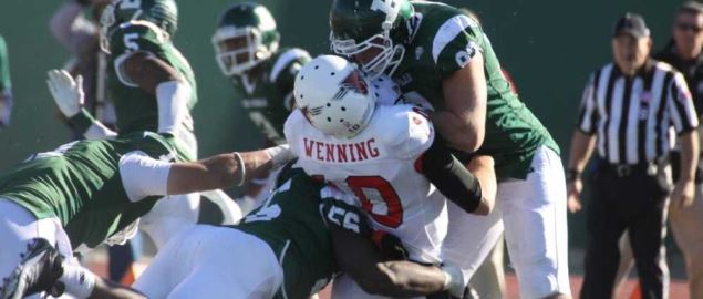 Ball State Cardinal player getting tackled in a 2011 game vs Eastern Michigan.