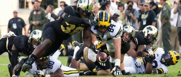 Purdue and Michigan players going after a fumbled ball in a 2017 regular season game.