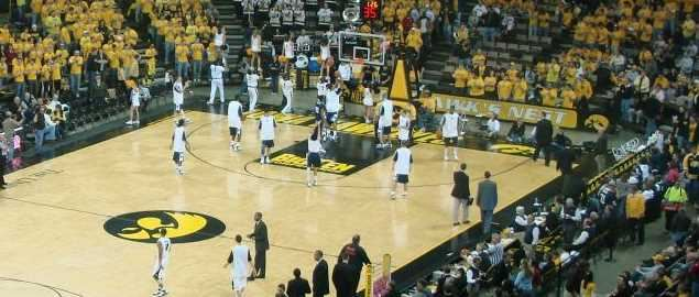 Iowa Hawkeyes and Penn State Nittany Lions men's basketball players warm up before a game.
